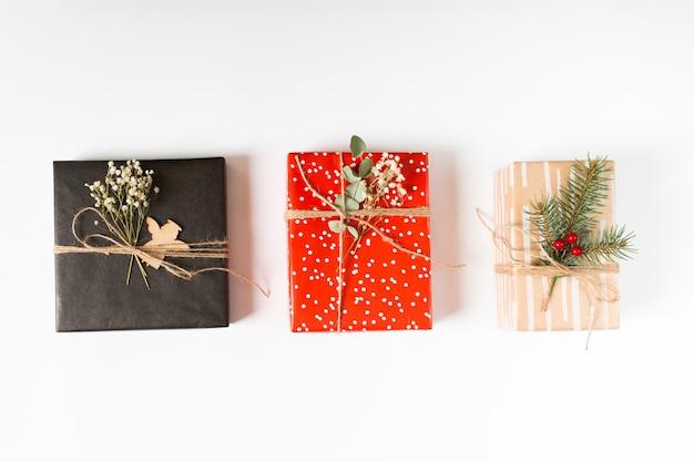 Coffrets cadeaux lumineux avec des branches sur la table Photo gratuit