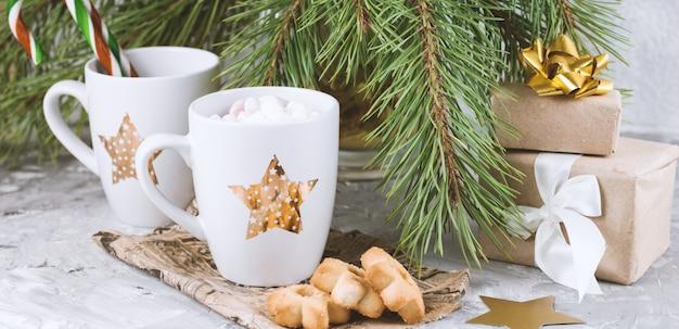 Coffrets cadeaux, mug avec boisson décorés de biscuits à la guimauve et en forme d'étoile près de branches d'arbres de noël à feuilles persistantes Photo Premium