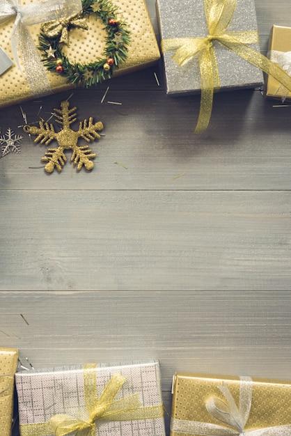Coffrets-cadeaux de noël brillant sur la conception de frontière de fond bois vue de dessus Photo Premium