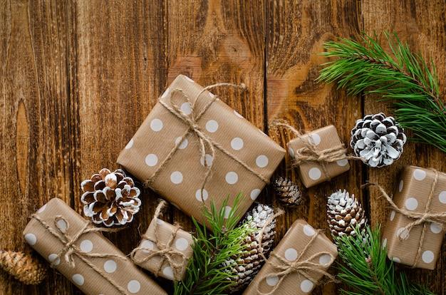 Coffrets-cadeaux de noël enveloppés dans du papier kraft, des cônes et des branches de sapin sur un fond en bois rustique. Photo Premium