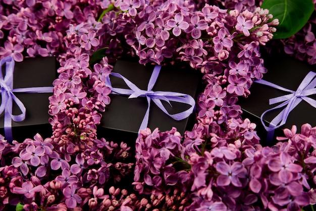 Coffrets-cadeaux noirs enveloppés d'un ruban violet avec du lilas naturel. Photo Premium