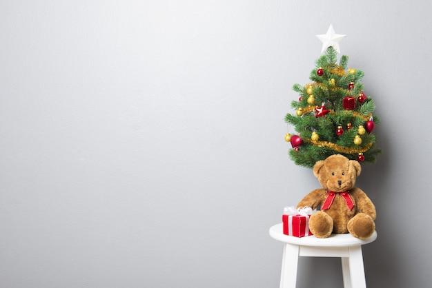 Coffrets Cadeaux, Ours En Peluche Et Petit Arbre De Noël Décoré Sur Une Chaise De Tabouret Photo Premium