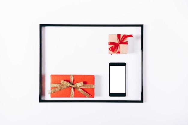 Coffrets cadeaux rouges avec rubans et téléphone portable dans un cadre Photo Premium