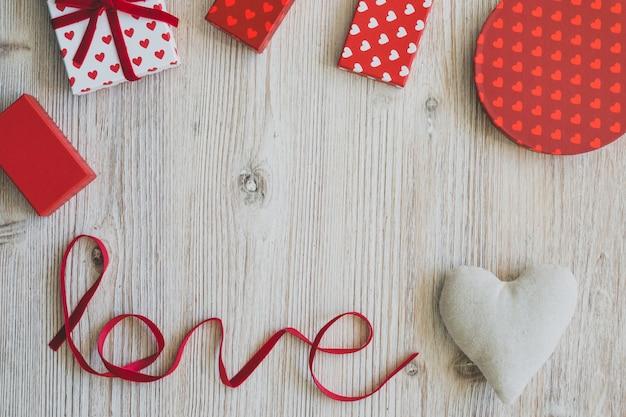 Coffrets cadeaux sur une table en bois avec le mot «amour» et un cœur Photo gratuit