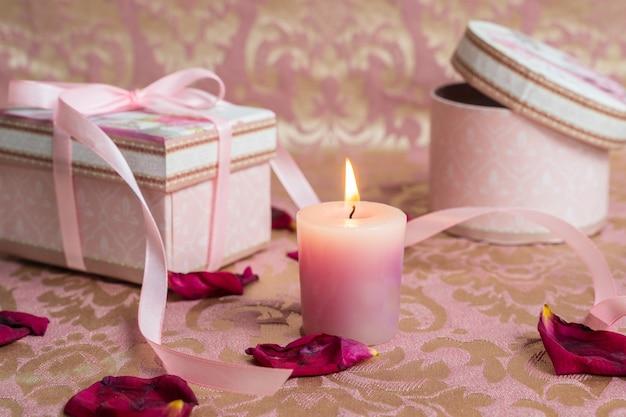 Coffrets roses avec une bougie sur des pétales de rose Photo Premium