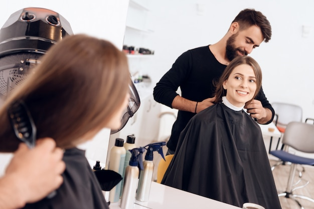 Le coiffeur coiffe la jeune femme aux cheveux bruns. Photo Premium