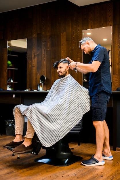 Coiffeur coiffer les cheveux d'un bel homme Photo gratuit