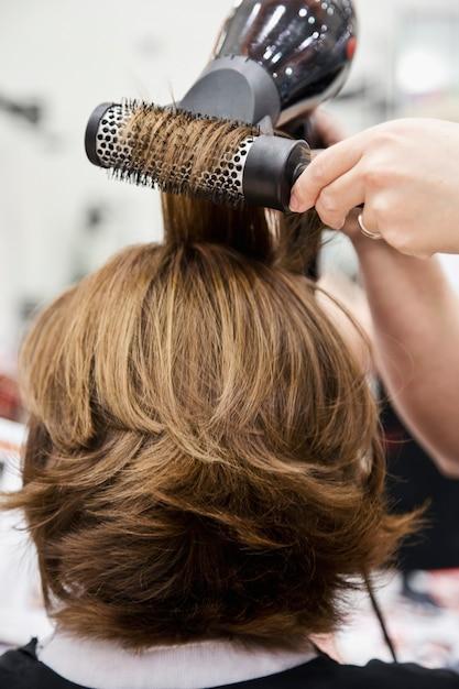 Le Coiffeur Coupe Et Peigne Les Cheveux Avec Un Sèche-cheveux à Une Femme Blonde Photo Premium