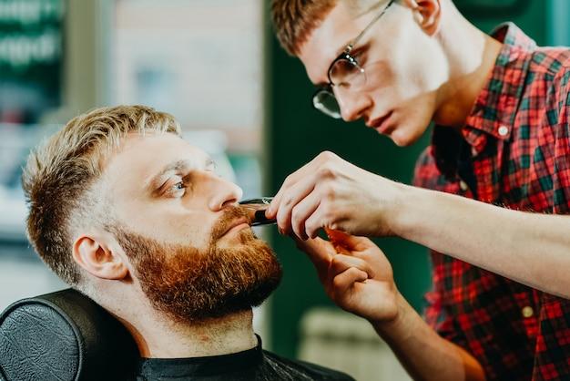 Le coiffeur coupe sa barbe à un homme dans le salon Photo Premium