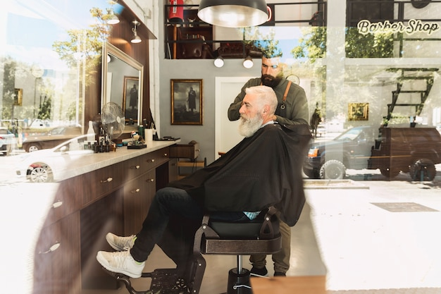 Coiffeur, couper barbe, vieux client, dans, salon coiffure Photo gratuit