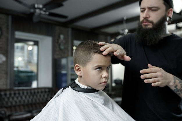 Coiffeur Enfants Coupe Petit Garçon Contre Un Noir Photo gratuit
