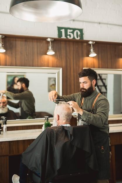 Coiffeur faisant la coupe de cheveux au client dans un salon de coiffure Photo gratuit