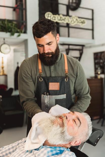 Un coiffeur fait sécher ses vieux clients après le rasage Photo gratuit