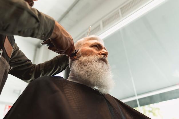 Coiffeur homme travaillant avec les cheveux d'un homme senior dans le salon de coiffure Photo gratuit