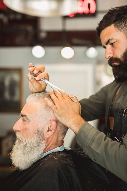 Coiffeur professionnel avec des ciseaux coiffant les cheveux du vieil homme Photo gratuit