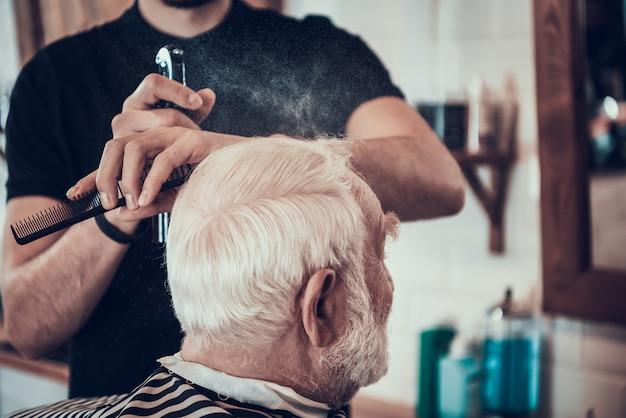 Le coiffeur rase les côtés adultes aux cheveux gris avec le rasoir Photo Premium