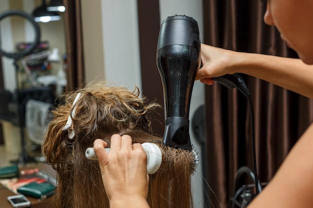 Le coiffeur sèche les cheveux au client avec un sèche-cheveux. Photo Premium