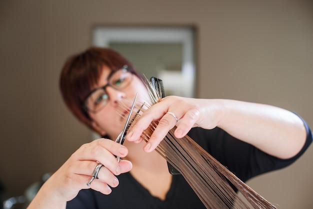 Coiffeur styliste faisant la coupe de cheveux gros plan de l'équipement de travail Photo Premium