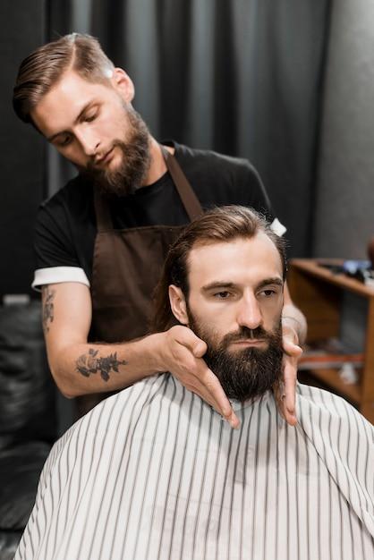 Coiffeur toilettant la barbe de l'homme dans le salon de coiffure Photo gratuit