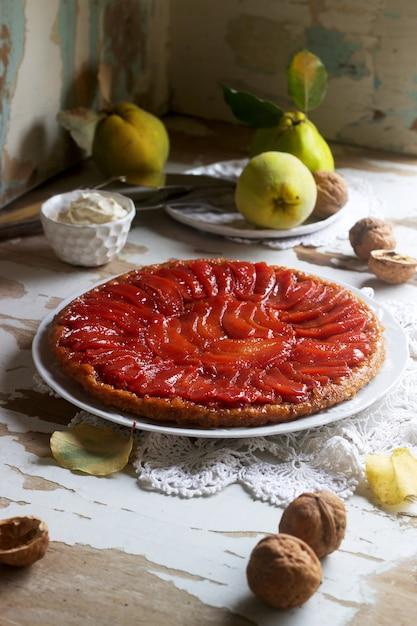 Coing tarte tatin servi avec de la crème fouettée, des fruits de coing et des noix sur une surface en bois. style rustique. Photo Premium