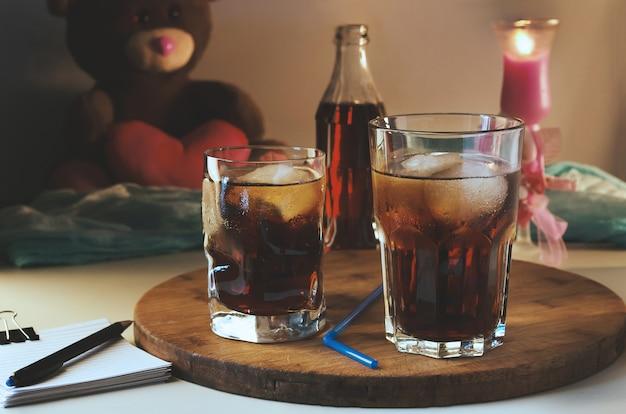 Cola Dans Un Verre Avec De La Glace Sur Le Fond D'une Bougie Allumée Et D'un Ours En Peluche. Photo Premium