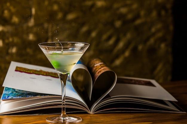 Colad martini avec vodka et une olive verte dans un verre cosmopolite Photo gratuit