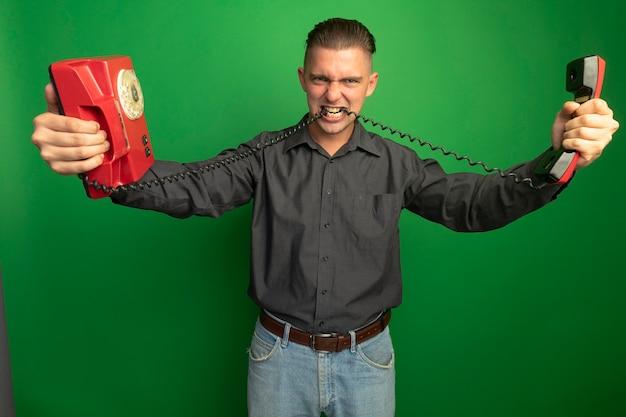 Colère Jeune Bel Homme En Chemise Grise Holding Vintage Phone Mordant Le Cordon Debout Sur Le Mur Vert Photo gratuit