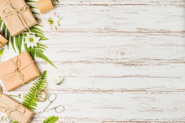 Colis brun noué avec ficelle et fleur blanche sur le bureau Photo gratuit