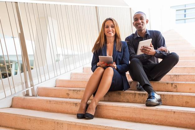 Collaborateurs tenant des tablettes et assis dans les escaliers Photo gratuit
