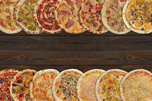 Collage Horizontal De Différentes Pizzas Cuites Au Four Sur Fond De Bois Foncé Photo Premium