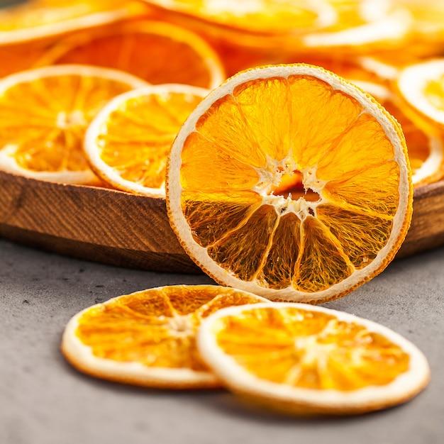 Collation Saine. Close-up De Tranches D'orange Séchée Sur Une Plaque De Bois. Photo Premium