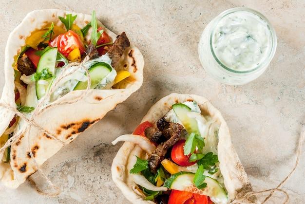 Collation saine, déjeuner. gyros sandwichs enveloppés grecs traditionnels - tortillas, pain pita avec une garniture de légumes, viande de boeuf et sauce tzatziki Photo Premium