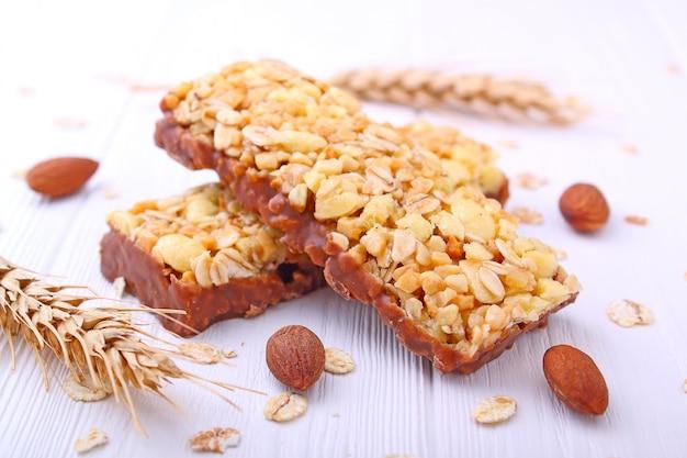 Collation santé, barres de muesli aux raisins secs et noix sur fond blanc Photo Premium