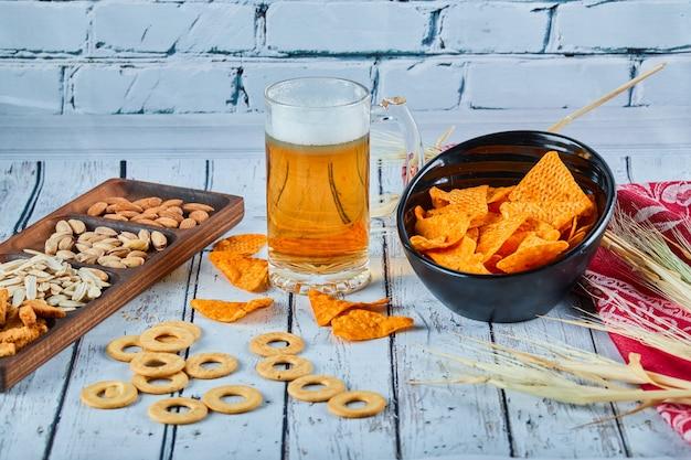 Collations Assorties, Chips Et Un Verre De Bière Sur Table Bleue. Photo gratuit