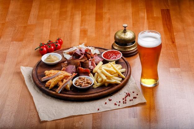 Des collations à la bière ou à l'alcool comprenant de la viande de porc fumée, des frites, du pain frit, des bâtonnets de crabe et des noix Photo Premium