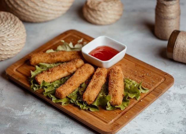 Collations de doigts de poulet croustillants, bâtonnets de ketcup sur une planche de bois Photo gratuit