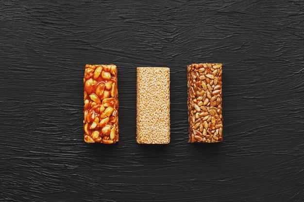 Collations santé. aliments de régime de remise en forme. barre de céréales avec des cacahuètes, du sésame et des graines sur une planche à découper sur une table sombre, barres énergétiques Photo Premium