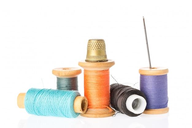 Collection de bobines de fil de couleur avec aiguille et dé à coudre isolé sur blanc. Photo Premium