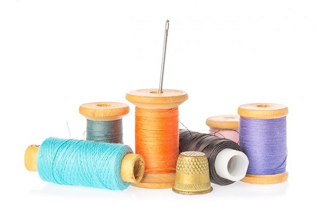 Collection de bobines de fil de couleur avec aiguille et dé à coudre isolé sur fond blanc. Photo Premium