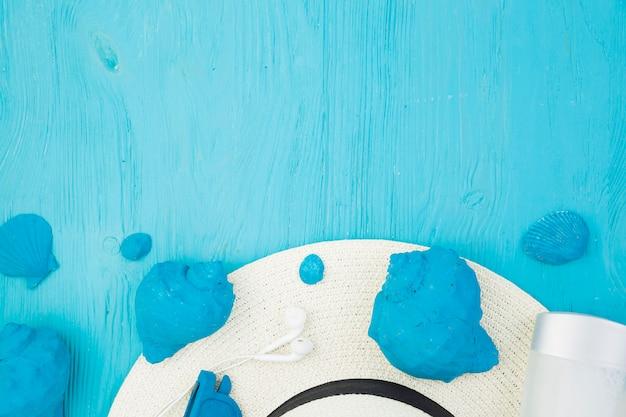Collection de coquillages bleus près du chapeau et des écouteurs Photo gratuit
