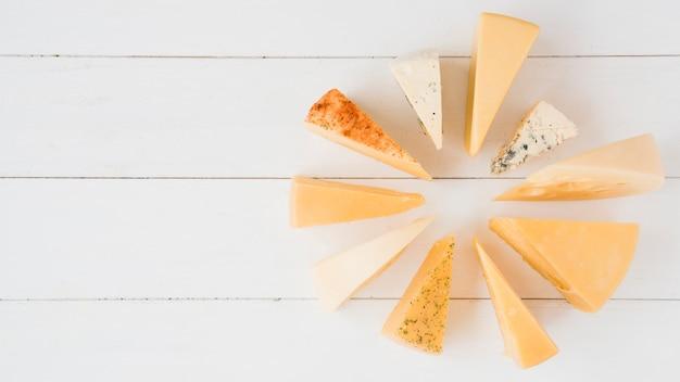 Collection de différents types de fromage sur une planche en bois blanche Photo gratuit