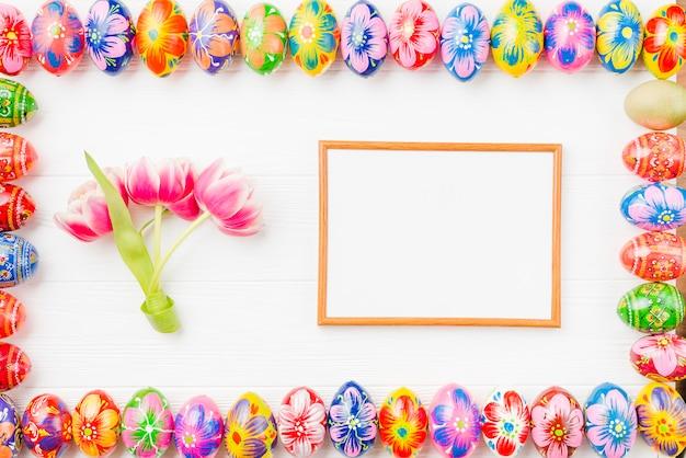 Collection d'oeufs colorés sur les bords, le cadre et les fleurs Photo gratuit