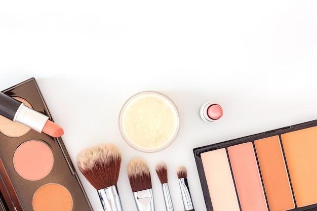 Une collection de pinceaux, de produits de maquillage et de produits de beauté cosmétiques disposés sur un fond blanc Photo Premium