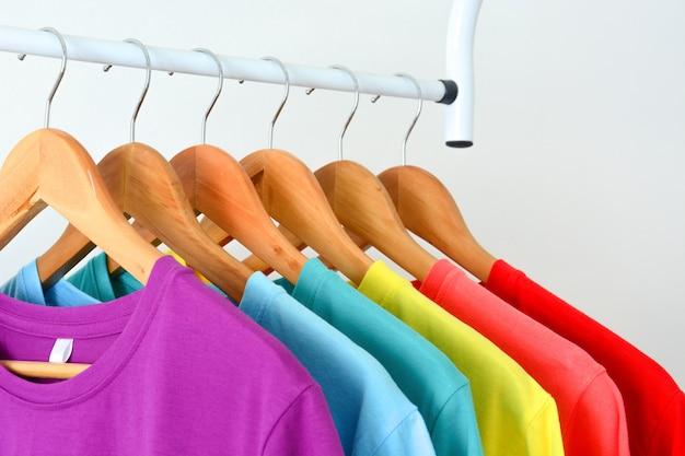 Collection de t-shirts colorés arc-en-ciel suspendus sur un cintre en bois sur un porte-vêtements Photo Premium
