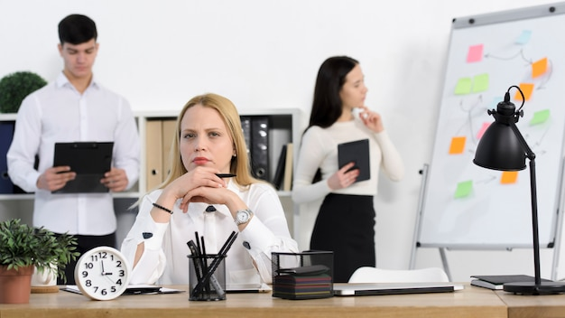 Collègue debout derrière la sérieuse jeune femme d'affaires au lieu de travail Photo gratuit