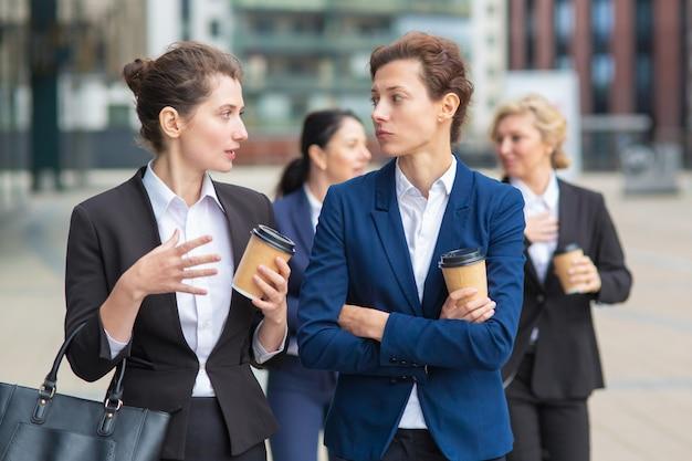 Collègues D'affaires Féminines Avec Des Tasses à Café à Emporter Marchant Ensemble Dans La Ville, Parler, Discuter D'un Projet Ou Discuter. Coup Moyen. Concept De Pause De Travail Photo gratuit