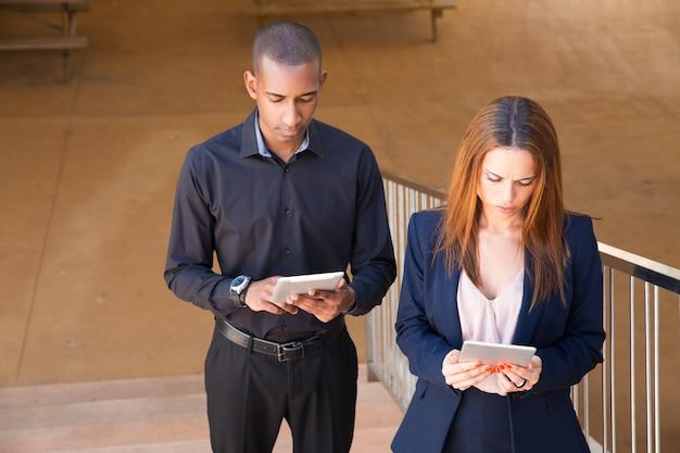 Des collègues concentrés lisant des nouvelles sur des tablettes dans des escaliers Photo gratuit