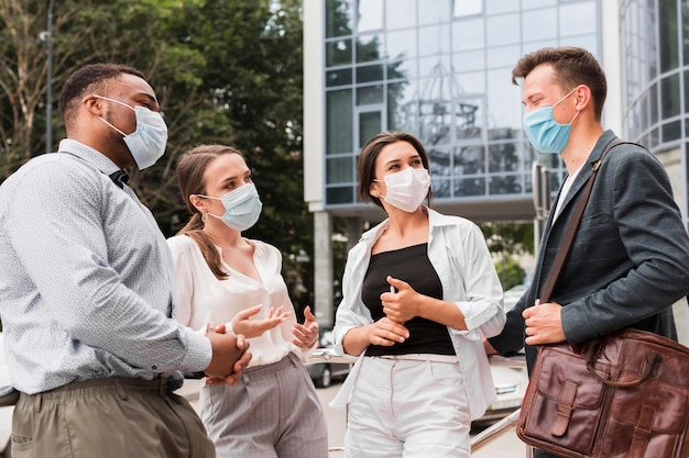Collègues Discutant à L'extérieur Pendant Une Pandémie Avec Des Masques Faciaux Photo gratuit