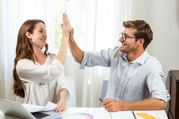 Collègues donnant haut cinq au bureau Photo Premium