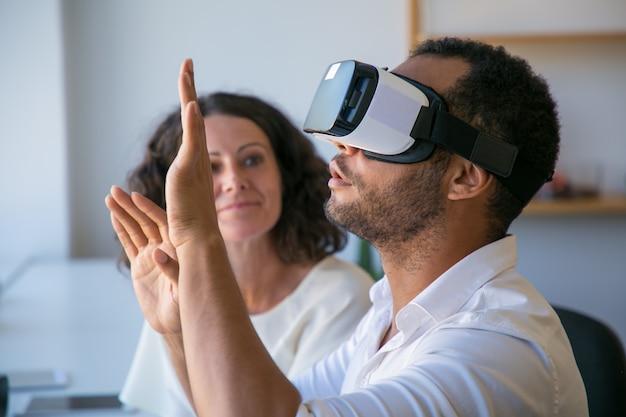 Des collègues enthousiastes testent ensemble un simulateur de réalité virtuelle Photo gratuit
